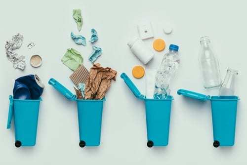 A flat lay of four blue trash cans laying on a white background with recycled items