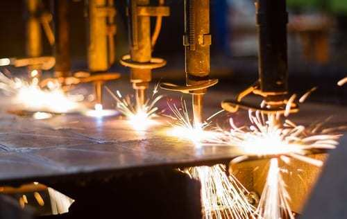 A closeup of a machine cutting steel with sparks
